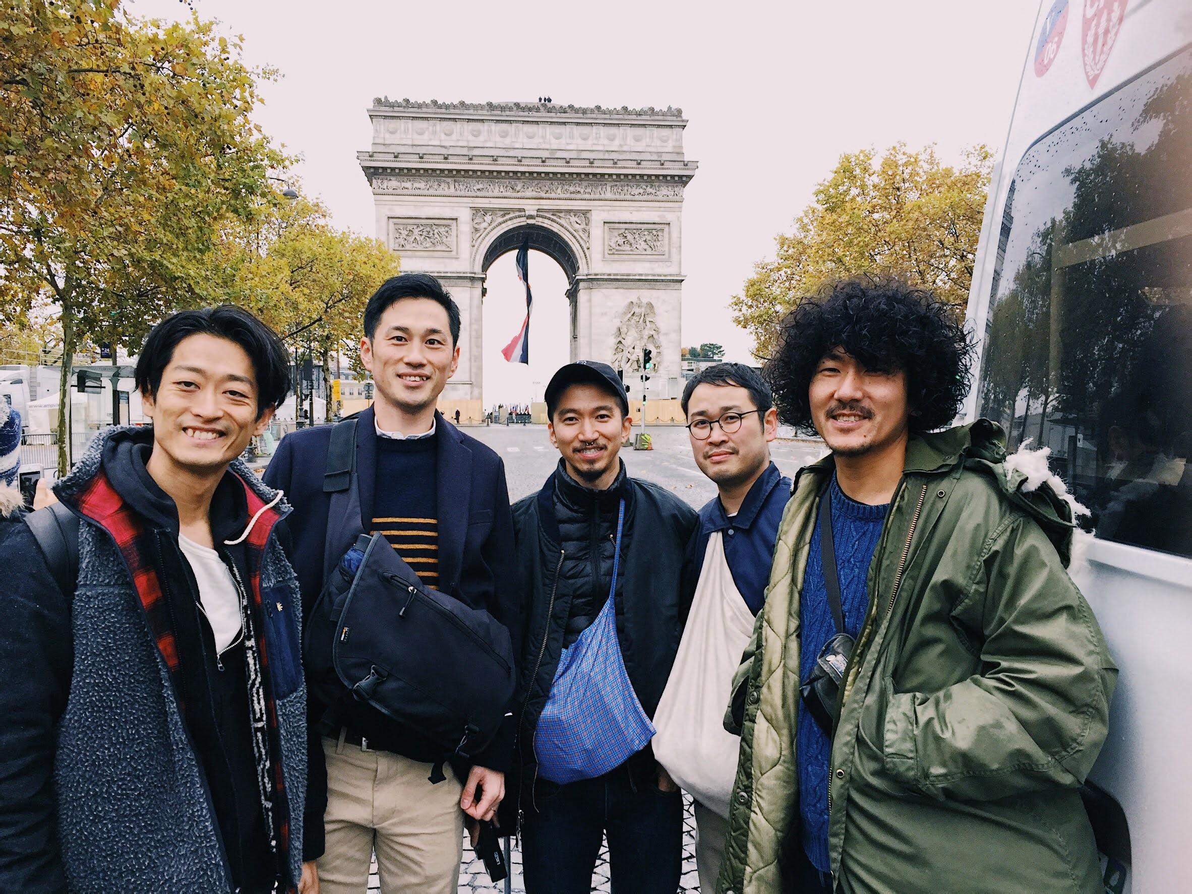 パリの凱旋門の前で仲間たちと